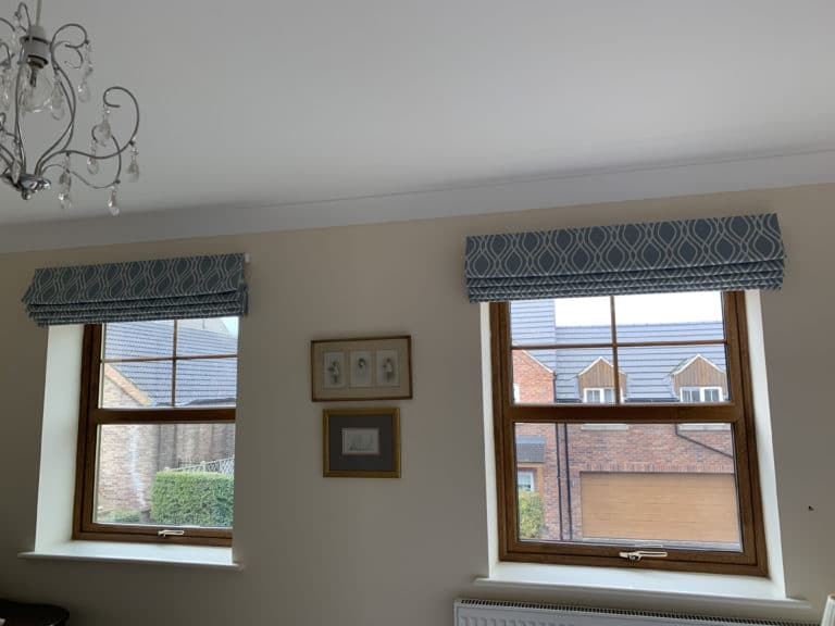 two windows with fabric blinds