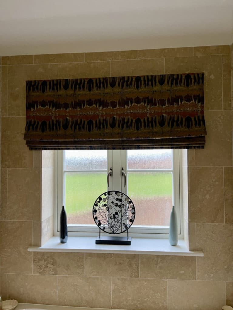 bathroom window with blind and decorations on window sill
